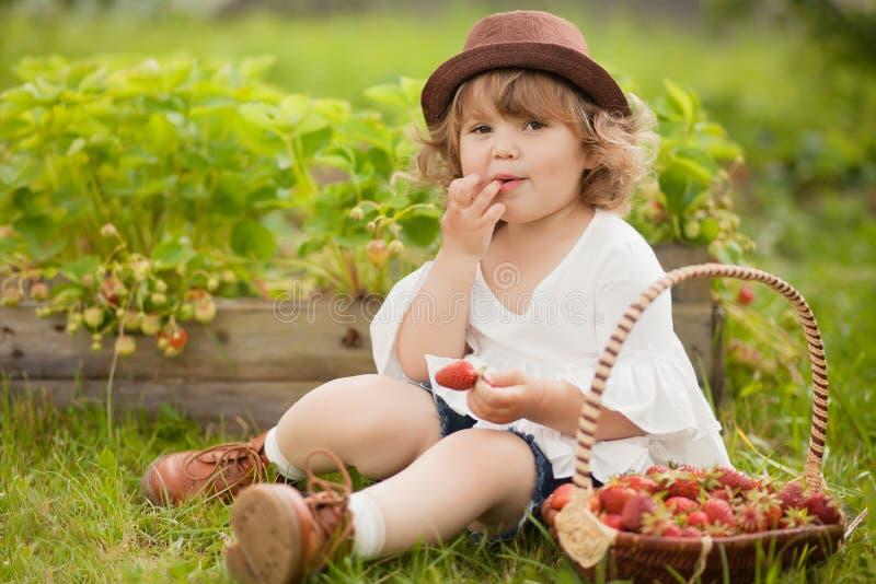 Милая маленькая девочка есть клубнику сидя на траве greeb стоковые фотографии rf