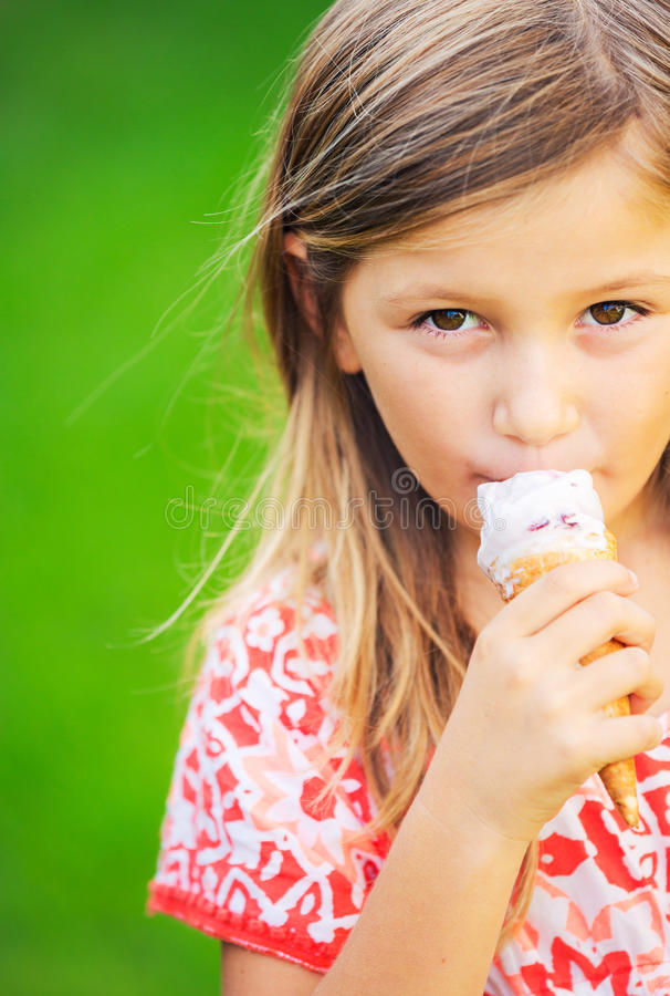 Милая маленькая девочка есть мороженое стоковое фото rf