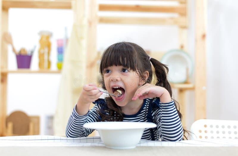 Милая маленькая девочка есть хлопья с молоком стоковое фото rf