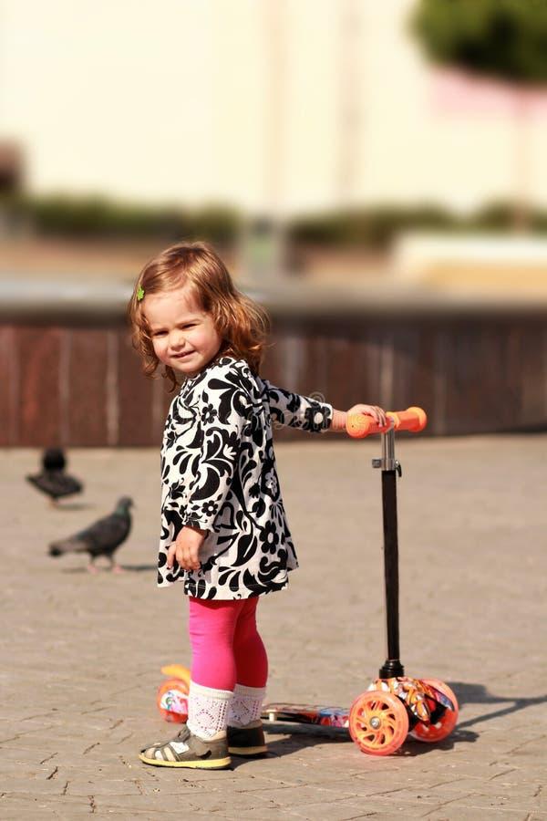 Милая маленькая девочка ехать самокат стоковые фотографии rf