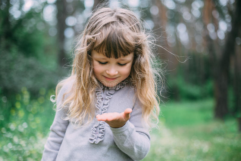 Милая маленькая девочка играя в зеленом парке стоковая фотография