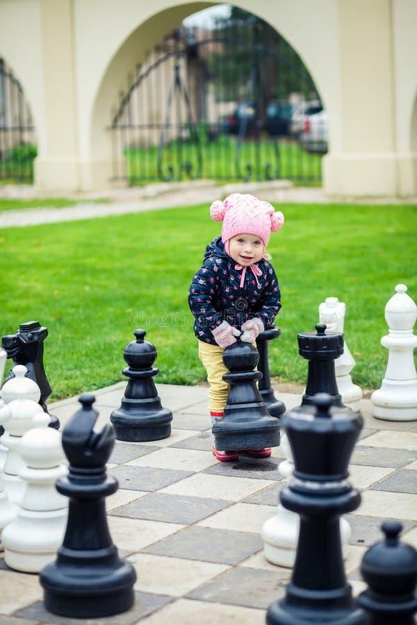 Милая маленькая девочка играя с гигантским шахмат стоковые изображения