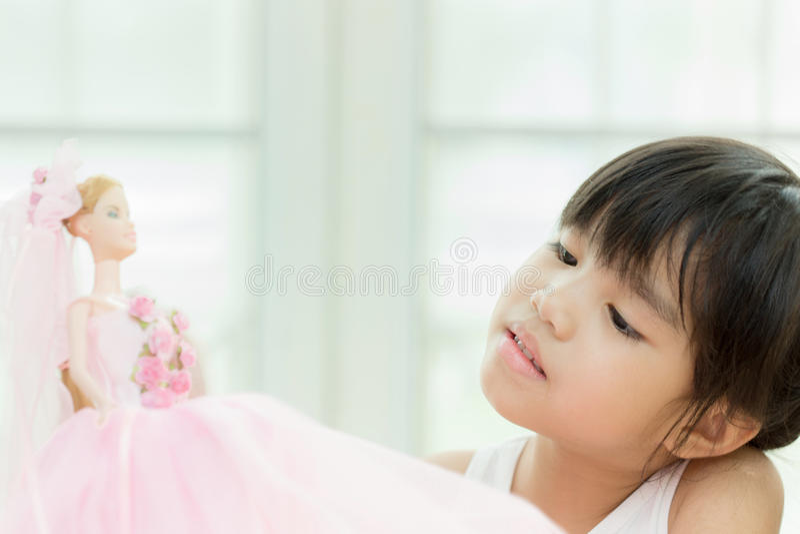 Милая маленькая девочка играя с куклой дома стоковая фотография rf