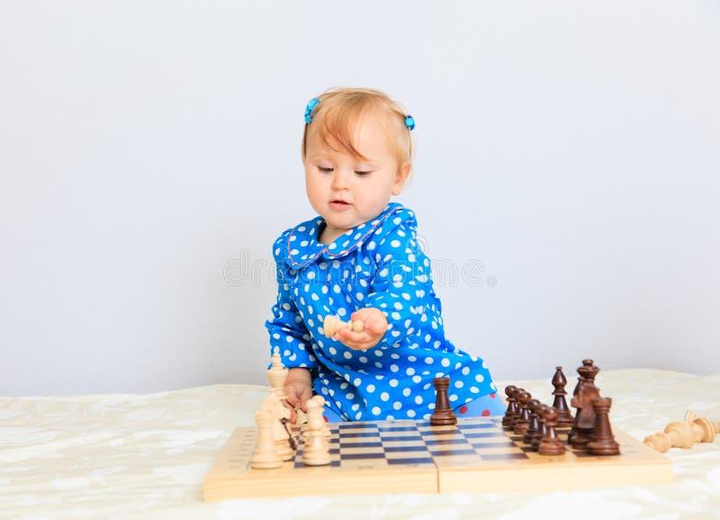 Милая маленькая девочка играя шахмат стоковая фотография rf