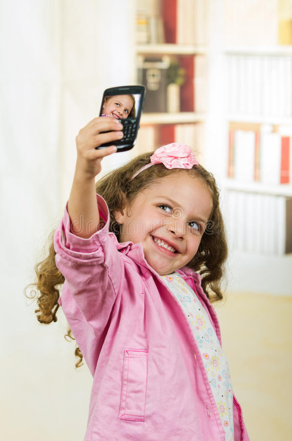 Милая маленькая девочка используя сотовый телефон принимая selfie стоковые фотографии rf