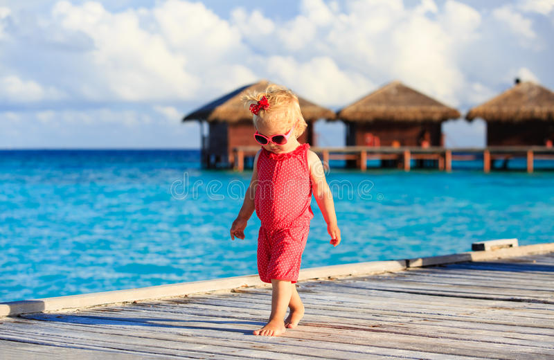 Милая маленькая девочка идя на пляжный комплекс стоковое фото rf