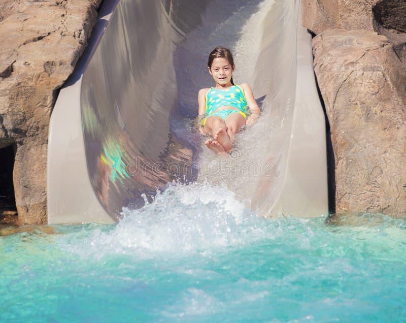 Милая маленькая девочка наслаждаясь влажной ездой вниз с водных горок стоковая фотография rf