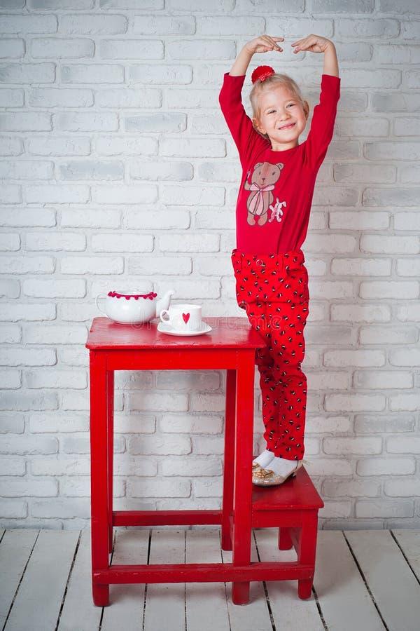 Милая маленькая девочка представляя около таблицы стоковое изображение rf