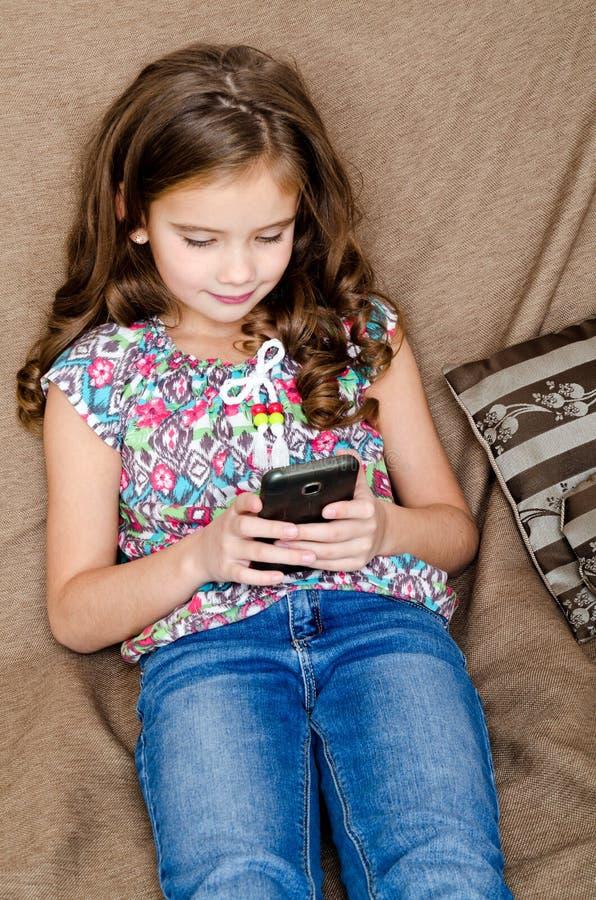 Милая маленькая девочка при мобильный телефон сидя на софе стоковое изображение