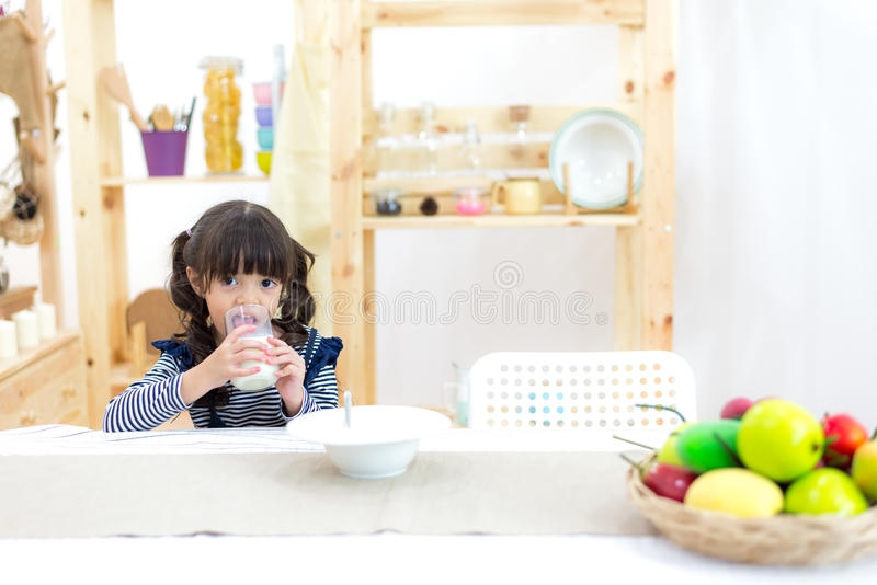 Милая маленькая девочка при усик молока держа стекло стоковые изображения