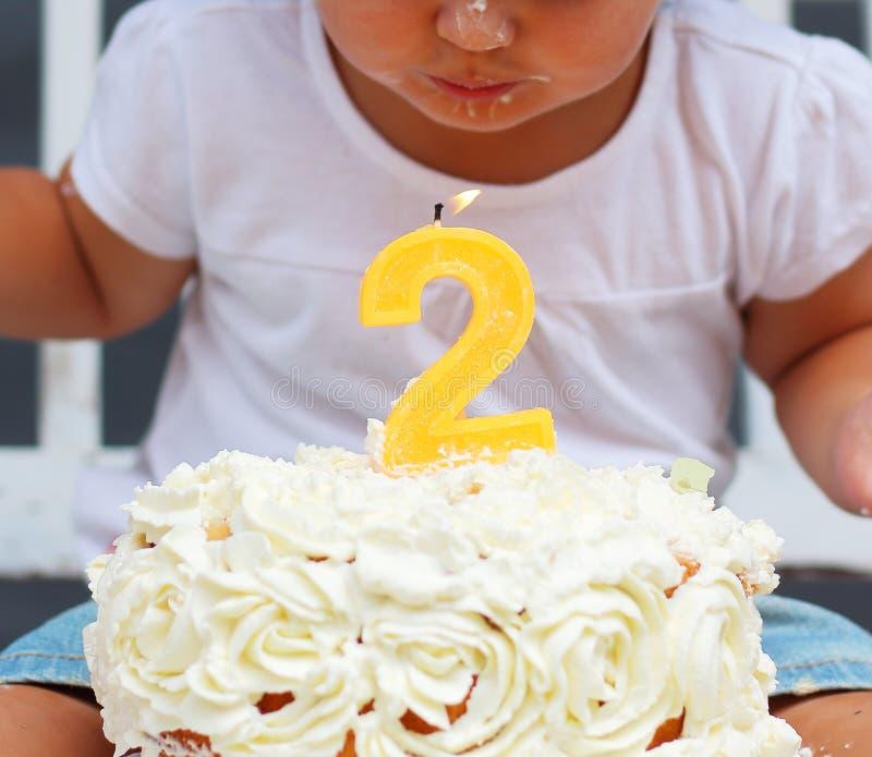 Милая маленькая девочка пробует дунуть свеча в ее втором торжестве дня рождения стоковая фотография rf
