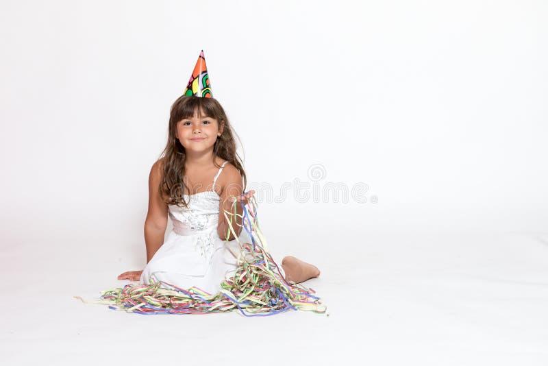 Милая маленькая девочка сидит на белой предпосылке стоковое изображение