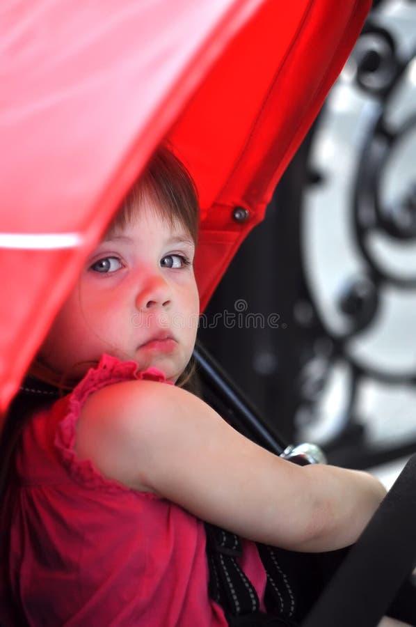 Милая маленькая девочка сидя в pram с селективным фокусом стоковые фото