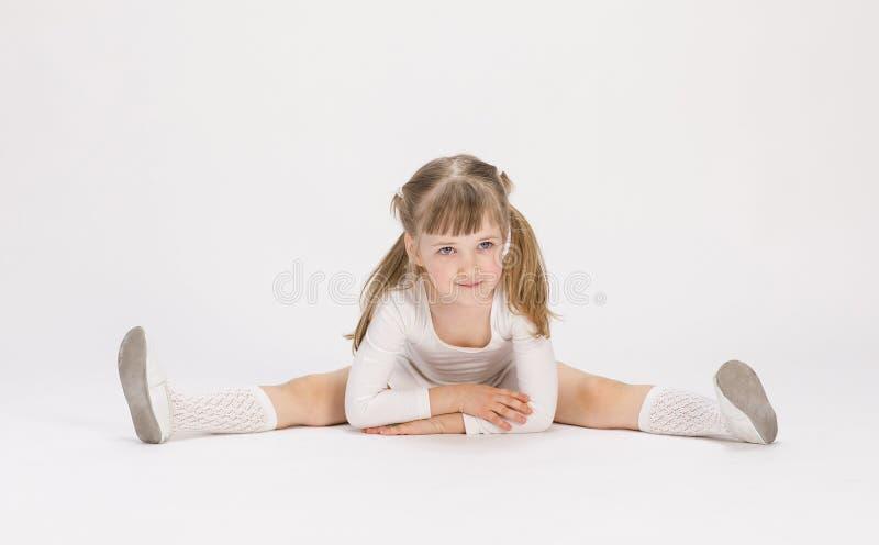 Милая маленькая девочка сидя на поле и делая тренировку стоковые фотографии rf