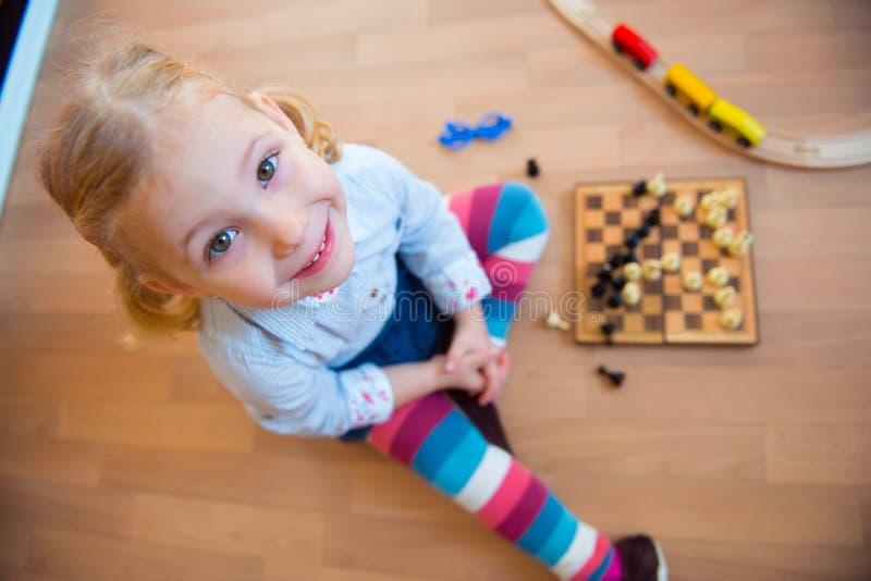 Милая маленькая девочка сидя на поле и играть стоковые изображения