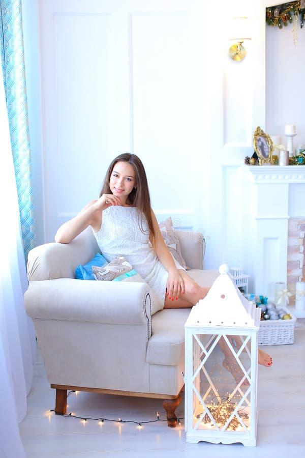 Милая маленькая девочка сидя около окна и представлений для фото в studi стоковое фото