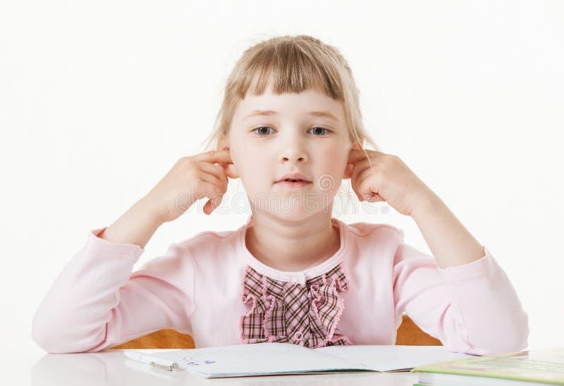 Милая маленькая девочка сидя с закрытыми ушами на столе школы стоковое изображение rf