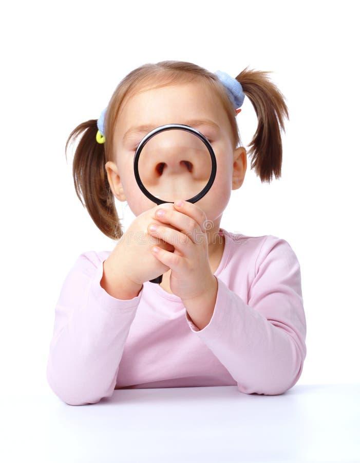 Милая маленькая девочка играет с увеличителем стоковое фото rf
