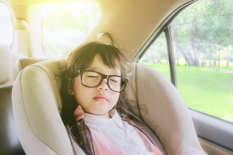 Милая маленькая девочка спать в автокресле стоковая фотография