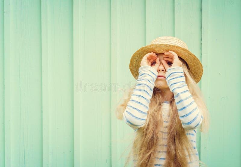 Милая маленькая девочка стоит около стены бирюзы в шляпе лодочника и смотрит изобретенные бинокли Космос для текста стоковое фото rf