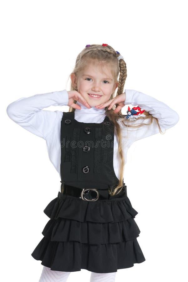 Милая маленькая девочка стоит против белизны стоковые изображения