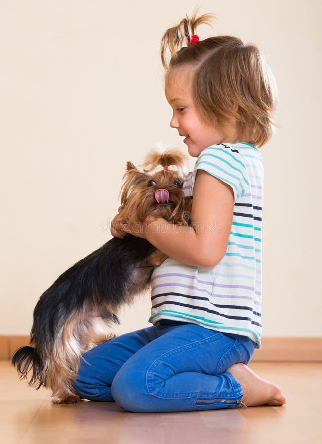 Милая маленькая девочка с йоркширским терьером крытым стоковая фотография