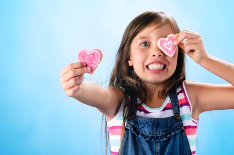 Милая маленькая девочка с печеньями формы сердца стоковое фото