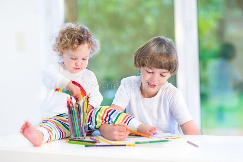 Милая маленькая девушка малыша наблюдая ее чертеж брата стоковые изображения
