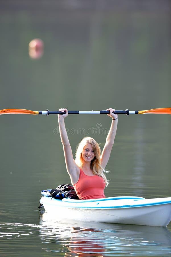 Милая молодая белокурая женщина - сплавляющся на каяке на озере стоковые изображения