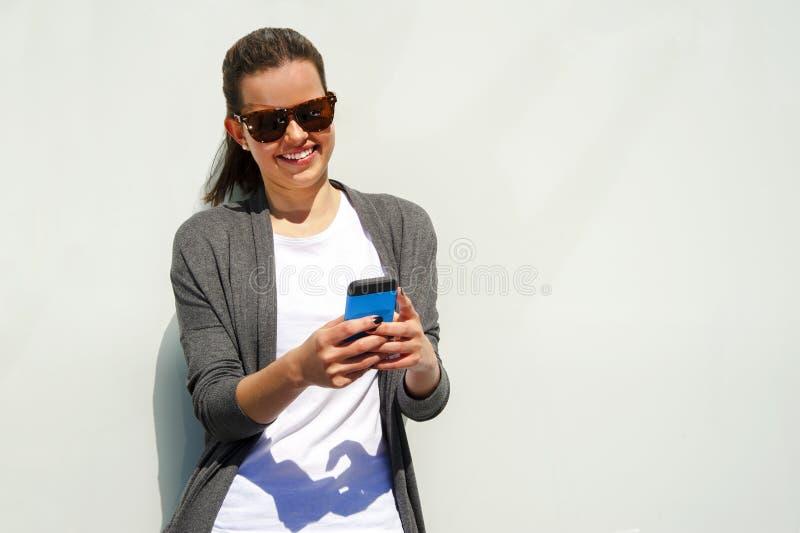 Милая молодая женщина используя мобильный телефон над белой стеной стоковое изображение rf
