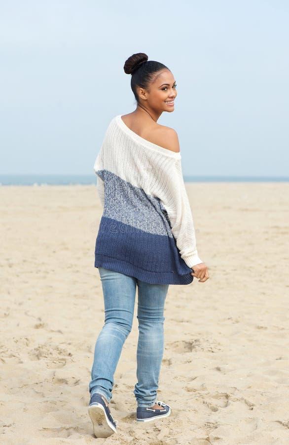 Милая молодая женщина идя на пляж и рассматривая плечо стоковое изображение rf