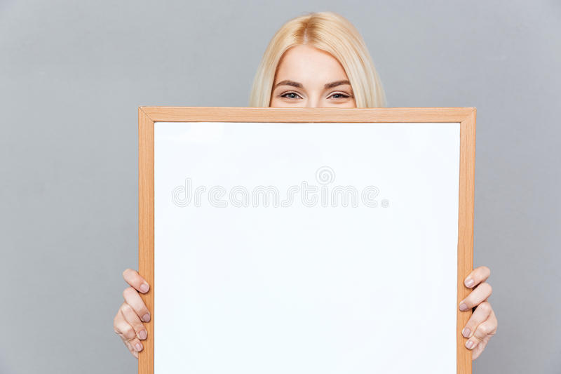 Милая молодая женщина пряча ее сторону за пустой белой доской стоковые изображения rf