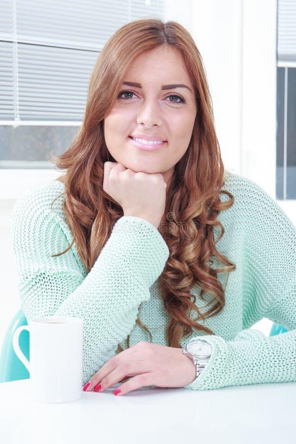Милая молодая женщина сидя с чашкой кофе стоковое фото rf