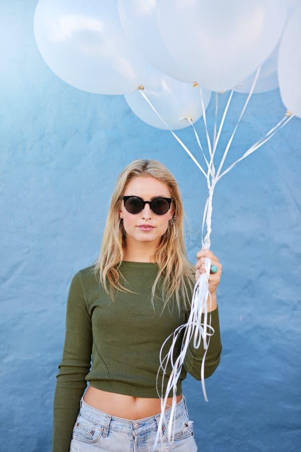 Милая молодая женщина с белыми воздушными шарами стоковое фото