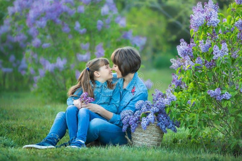 Милая прелестная красивая женщина мамы дамы матери с дочерью девушки брюнет в луге куста пурпура сирени Люди в носке джинсов стоковая фотография