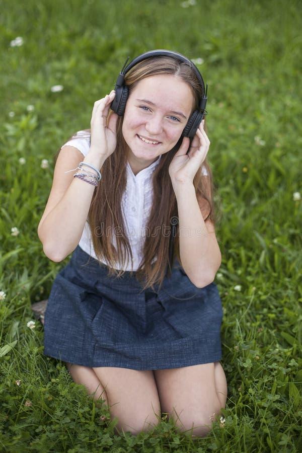 Милая предназначенная для подростков девушка в наушниках наслаждается музыкой на зеленой траве в парке полюбите нот стоковые фотографии rf
