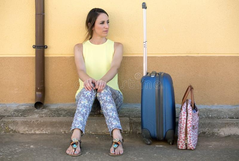 Милая путешествуя женщина при чемодан ждать в улице стоковое изображение