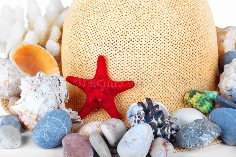 Милая соломенная шляпа с морскими звёздами, камешком и мидией стоковое изображение rf