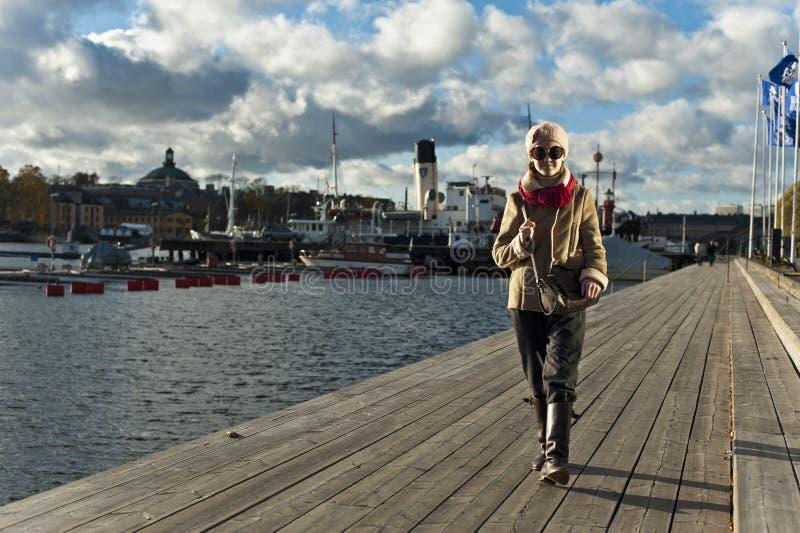 Милая стильная девушка идя на пристань в Стокгольме стоковая фотография