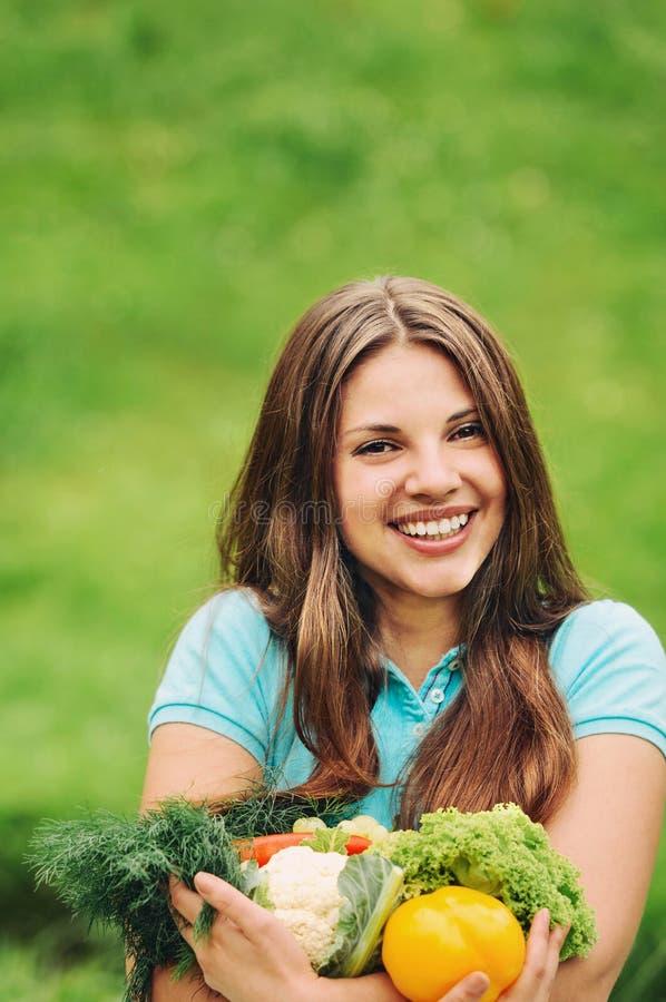 Милая счастливая женщина с органическими здоровыми фруктами и овощами на t стоковая фотография rf