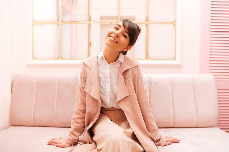 Милая усмехаясь девушка в пальто сидя на софе стоковое фото rf