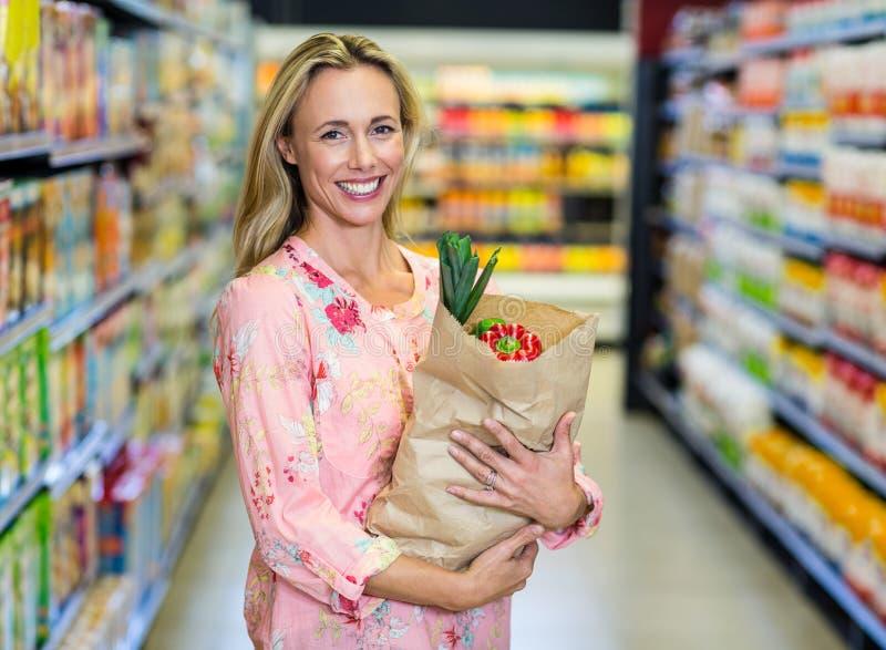 Милая усмехаясь женщина держа продуктовую сумку стоковое изображение rf
