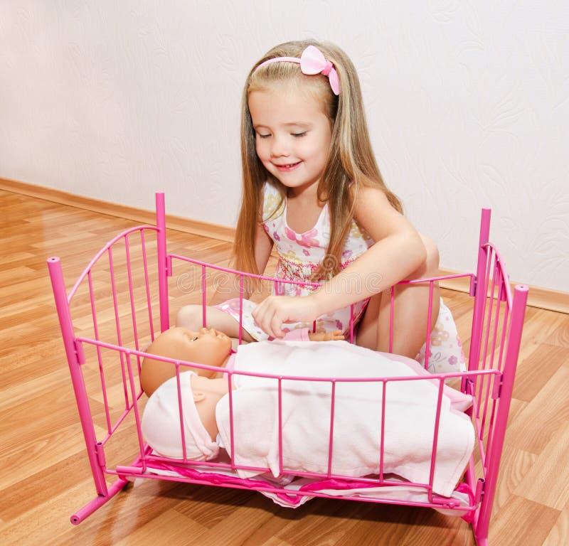 Милая усмехаясь маленькая девочка играя с ее newborn куклами младенца стоковое изображение