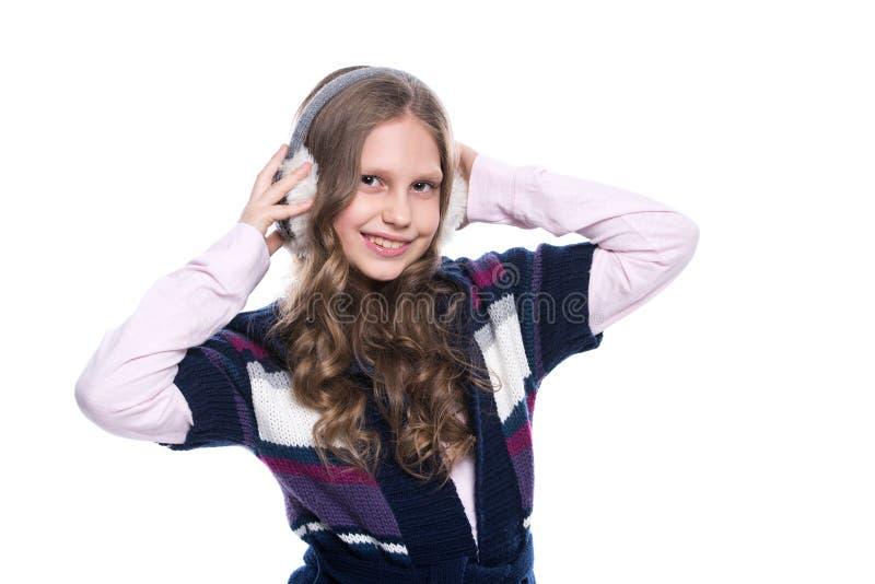 Милая усмехаясь маленькая девочка при курчавый стиль причёсок нося красочный свитер и головной убор изолированный на белой предпо стоковая фотография rf