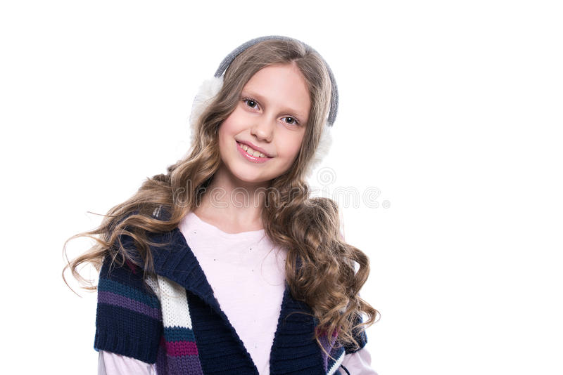 Милая усмехаясь маленькая девочка при курчавый стиль причёсок нося красочный свитер и головной убор изолированный на белой предпо стоковые изображения