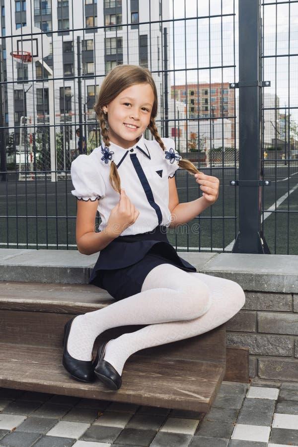 Милая школьница в форме на спортивной площадке стоковые изображения rf