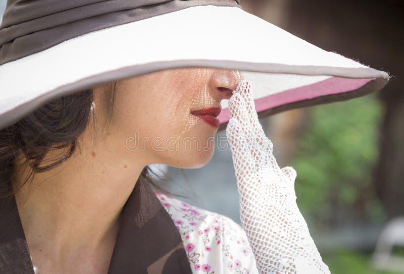 Милая эра 1920s одела девушку с шляпой и перчатками стоковое фото