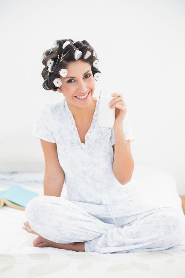 Милое брюнет в роликах волос держа стекло молока усмехаясь на стоковое фото