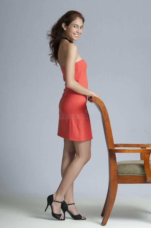 Милое брюнет стоя вкратце платье стоковое фото