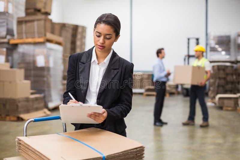 Милое сочинительство менеджера склада на доске сзажимом для бумаги стоковое фото rf
